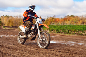 Motocross, enduro rider on dirt track. The forest behind him