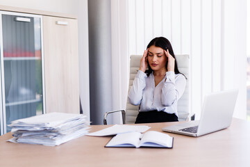 Businesswoman having headache in her office after doing very hard work