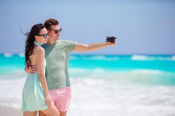 Happy couple taking a photo on white beach on honeymoon holidays