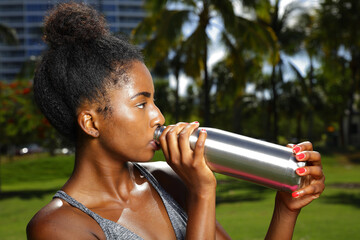 Fitness model posing with a water bottle in the park