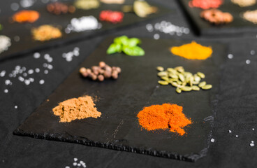 Large selection of different colorful contrast spices and seeds on slate against black background