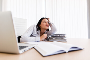 Woman at her work desk dreaming about something beautiful