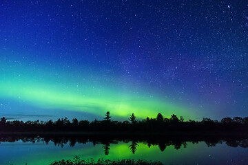 Night sky full of stars and a hint of the Milky Way galaxy above beautiful green Northern Lights