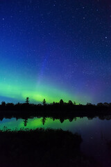 Northern Lights dancing over silhouetted night landscape, colours shooting up into a sky full of stars and reflected in still lake