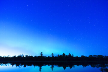 Early night sky with trees silhouetted and reflecting in calm waters, stars and northern lights just beginning