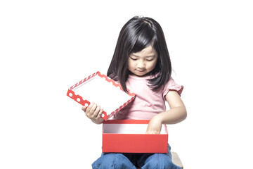A little girl portrait with smile hold a red gift box isolated white.