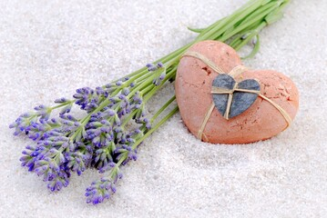 Summer background for holiday time. Card with white sand, heart and lavender flowers.