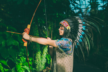 Red Indian woman portrait outdoors. Bow and arrows. Hunter in the jungle. American Indian style. Attractive boho woman.