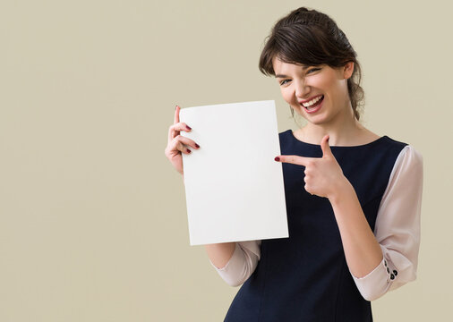 Portrait of young pretty business woman in white and blue suit shows piece of paper  on background.