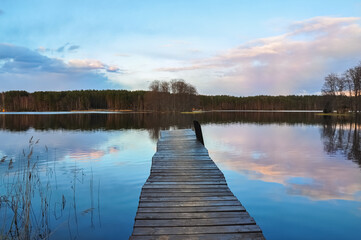 Photo sur Aluminium Ponts Panorama landscape. Wooden pier on the lake at sunset, clouds reflection in the water.