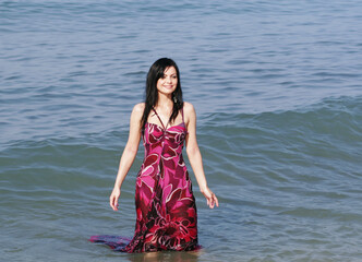 smiling woman standing in sea waves