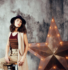 young pretty woman waiting alone in modern loft studio, hipster in hat, fashion musician concept, lifestyle people
