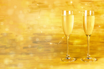 Two glasses of champagne on blurred golden background