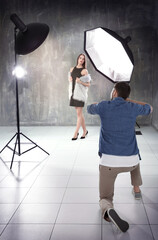 Young beautiful model posing for professional photographer in studio