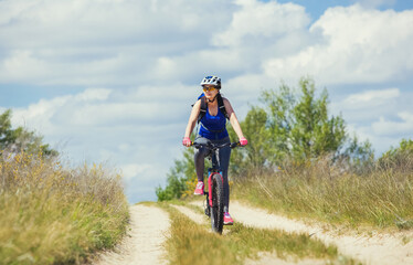 One young woman - an athlete rides on a mountain bike outside of town on the road in the forest on a summer day.