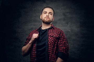 Bearded hipster male dressed in a red fleece shirt over grey background.