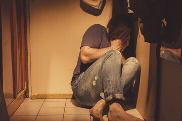 Man sitting in a corner, sad, depressed and lonely, crying