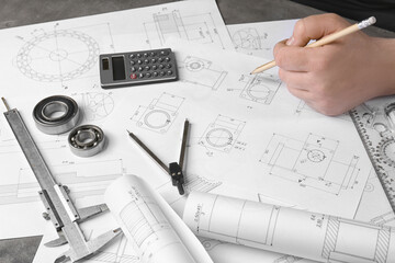 Engineer working with part blueprints on workplace