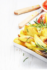 Grilled potato  with rosemary on white wooden table.