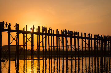 Silhouettes of people on U Bein bridge over the Taungthaman Lake at sunset, in Amarapura, Mandalay, Myanmar