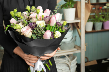 Woman holding beautiful blooming bouquet of flowers in shop
