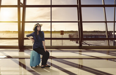 Tired asian traveler woman sitting on luggage waiting flight
