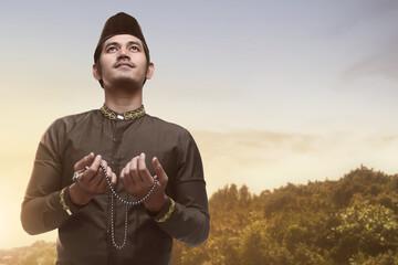 Handsome asian muslim man holding prayer beads and praying