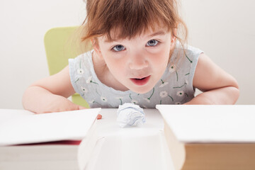 The child blows on a ball of paper at the table.