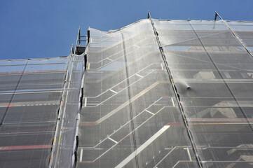Gerüst für die Renovierung der Fassade eines Verkaufsgebäudes mit Sicherheitsnetz
