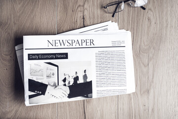 Newspaper with eyeglasses on table