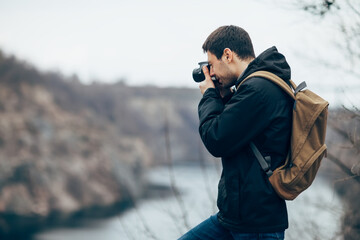 Handsome man takes pictures of nature