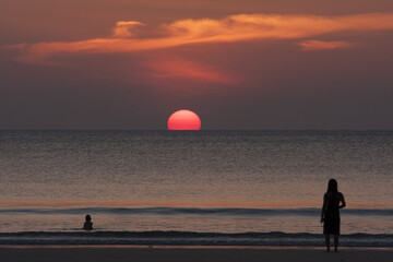 Lady and boy enjoying beautiful sunset on the beach for holiday time, silhouette sunset at   the sea, selective focus