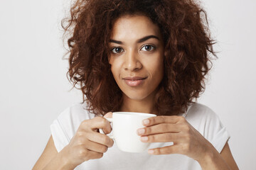 Portrait of beautiful african girl smiling holding cup of coffee looking at camera.