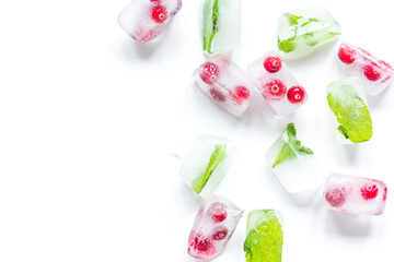Ice cubes with berries and mint white background top view mock up