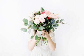 Pretty woman with beautiful flowers bouquet: bombastic roses, blue eringium, anthurium flower, eucalyptus branches at white wall. Front view. Floral lifestyle composition.