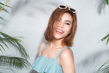 Beauty summer. Beautiful asian woman between palm leaves.