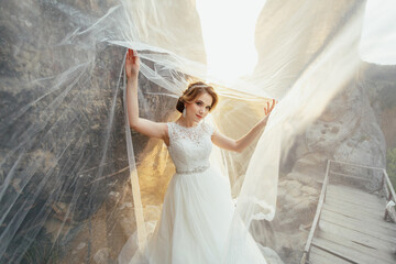 Golden sun illuminates stunning bride posing on the hill