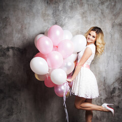 Charming young blonde in a white dress with pink sash, holding a large bundle of balloons. On gray textured background