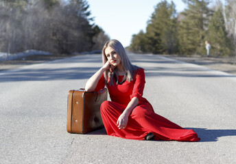 Young woman in red dress on road with red luggage