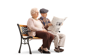 Seniors sitting on bench with one of them reading newspaper
