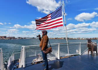 Man at Boston waterfront and United States national flag MA