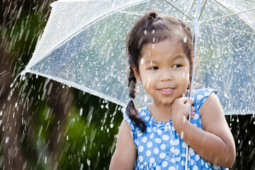 Portrait of cute asian little girl with umbrella in rain