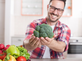 Man showing vegetables in kitchen