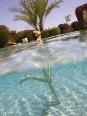 femme souriante en maillot de bain au bord d'une piscine