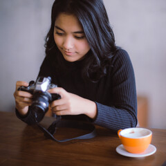 Asian woman holding Vintage camera on her holiday, Vintage color