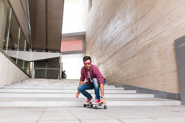 Trendy man riding skateboard