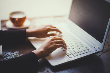 Hand of woman working with her Laptop and Coffee by the side