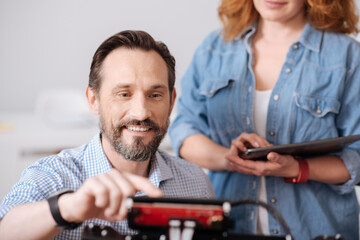Cheerful delighted man pressing a button