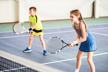 Happy children playing sport game on court
