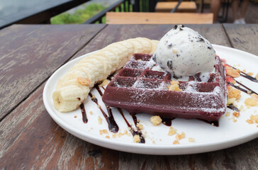 chocolate waffles with vanilla ice cream, banana, whipped cream and strawberry syrup